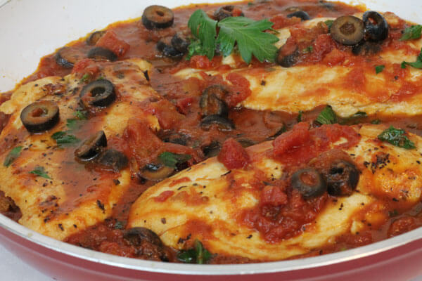 chicken cooked in a skillet with tomatoes, garlic and black olives