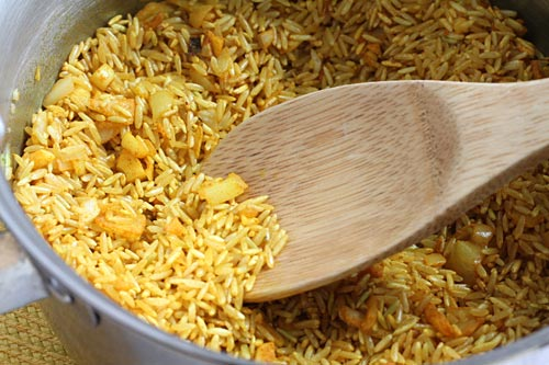 yellow rice in the pan with onions