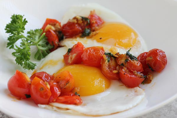 Sauteed Cherry Tomatoes over cooked eggs