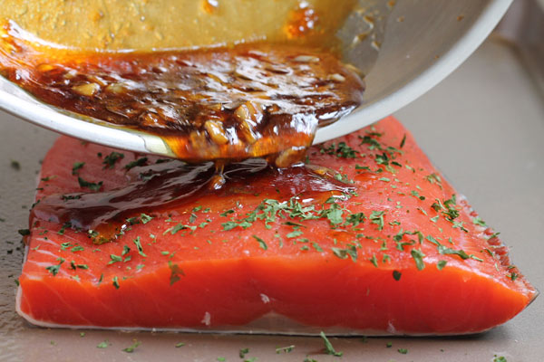 pouring glaze over the salmon