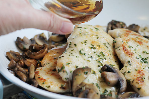 pouring marsala wine over chicken