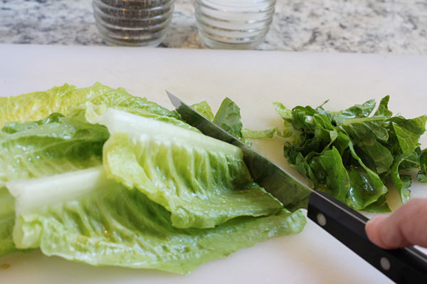 romaine lettuce being sliced for summer salad
