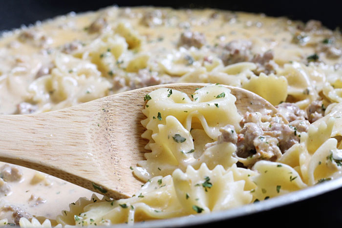 bow tie pasta in the skillet with the sausage