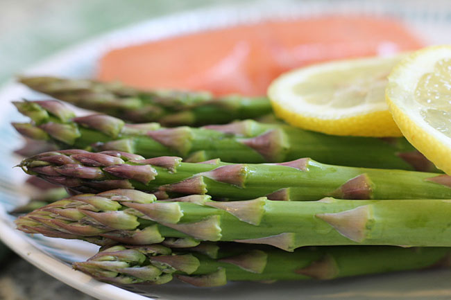 fresh asparagus on a plate with uncooked salmon and lemon