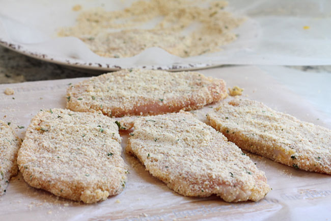 breaded pork chops on waxed paper