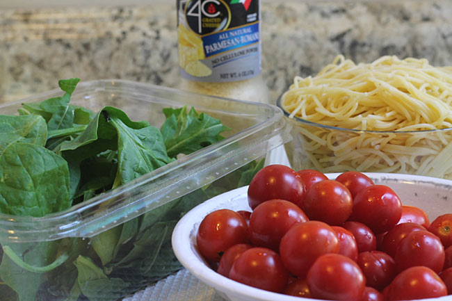 Container of baby spinach and arugula, cherry tomatoes and pasta